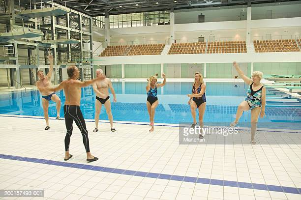 group of senior people exercising at poolside - old man in speedo stock photos and pictures