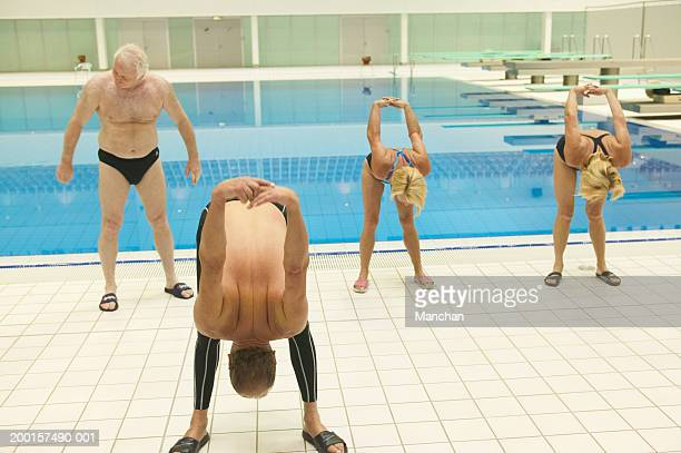 group of senior people stretching at poolside - old man in speedo stock photos and pictures
