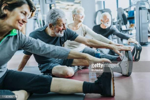 grupo de povos sênior que esticam seus pés em uma ginástica. - perna humana - fotografias e filmes do acervo