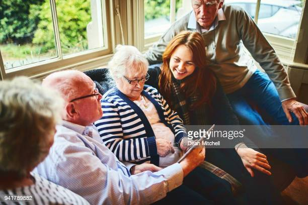 Group of senior people with young woman using digital tablet