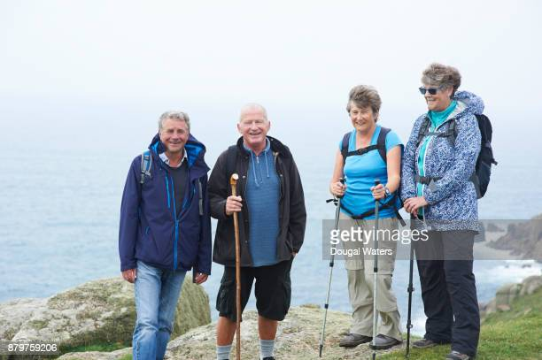 Group of senior ramblers on rocky coastal viewpoint, UK.