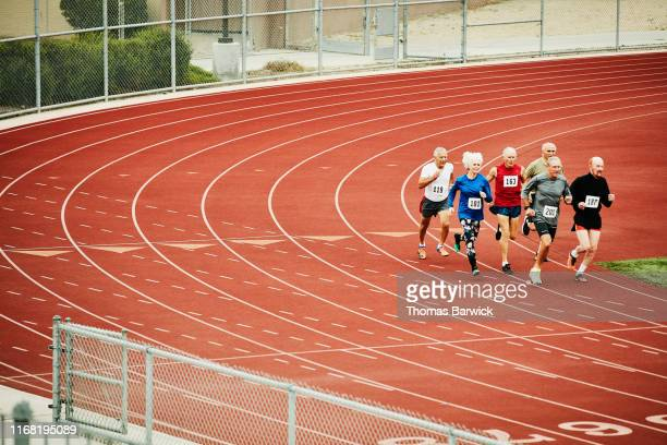 group of senior track athletes running distance race on track - forward athlete stock pictures, royalty-free photos & images