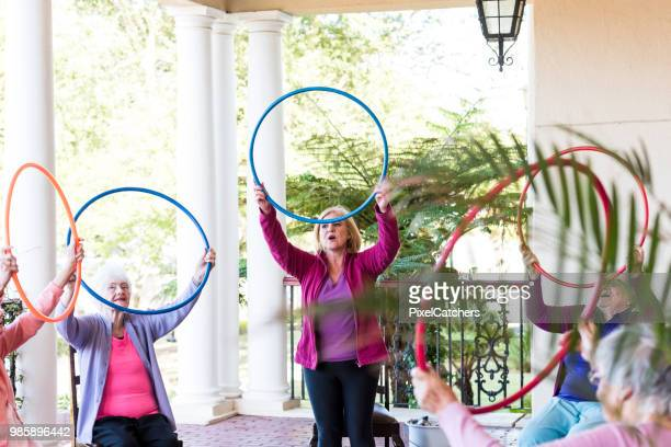 Een groep van senior vrouw op een fitness klasse kunststof hoepels boven hun hoofd houden