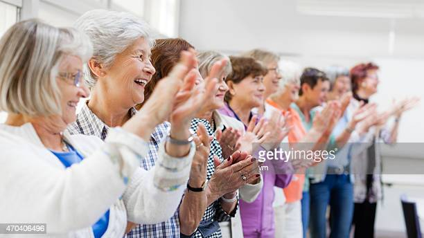 group of senior women applauding - community center stock pictures, royalty-free photos & images