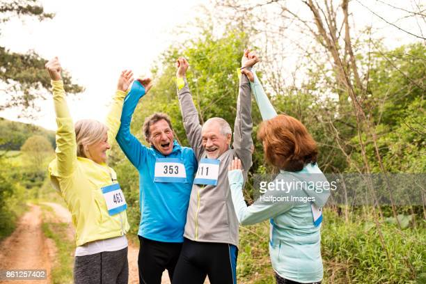 Group of seniors celebrating after the race together in nature.