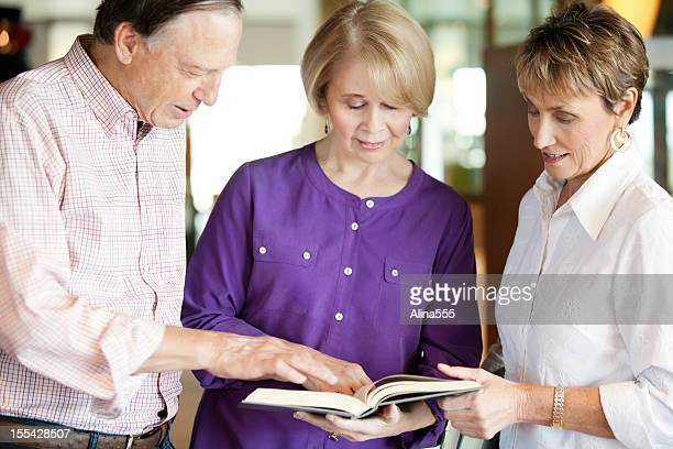 group of seniors checking out information in a book - alina stock pictures, royalty-free photos & images