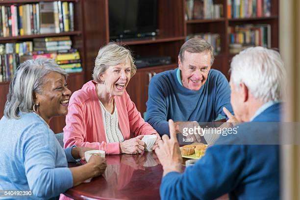Grupo de jubilados conversa, Riendo café