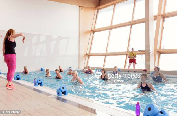 group of seniors doing water aerobics - leisure facilities stock pictures, royalty-free photos & images