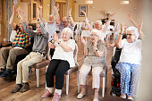 Group Of Seniors Enjoying Fitness Class In Retirement Home
