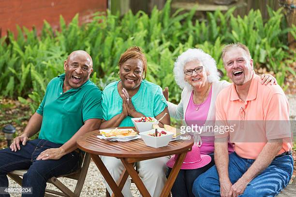 Group of seniors enjoying food and friends in back yard