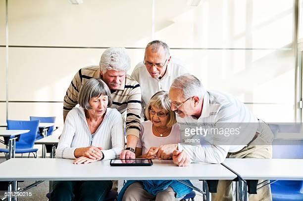 Grupo de seniores examinar digital tablet