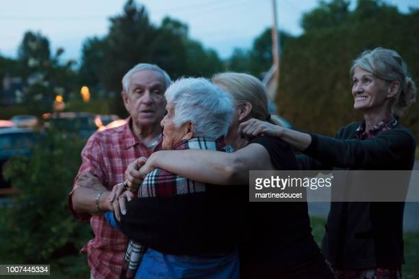 """group of seniors having a tender moment outdoors at dusk. - """"martine doucet"""" or martinedoucet stock pictures, royalty-free photos & images"""
