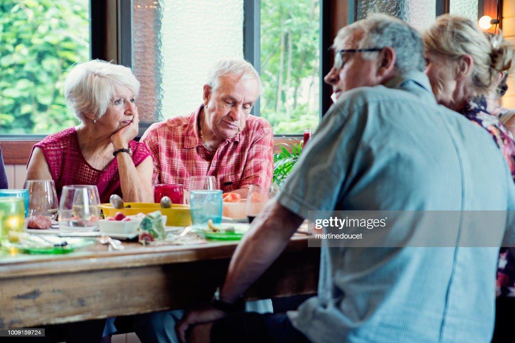 Group of seniors having dinner in summer house. : Stock Photo