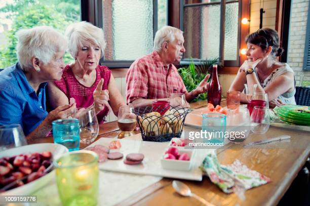 """group of seniors having dinner in summer house. - """"martine doucet"""" or martinedoucet stock pictures, royalty-free photos & images"""