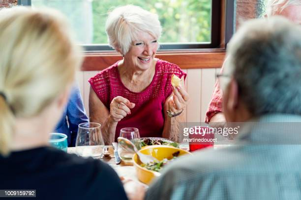 Group of seniors having dinner in summer house.