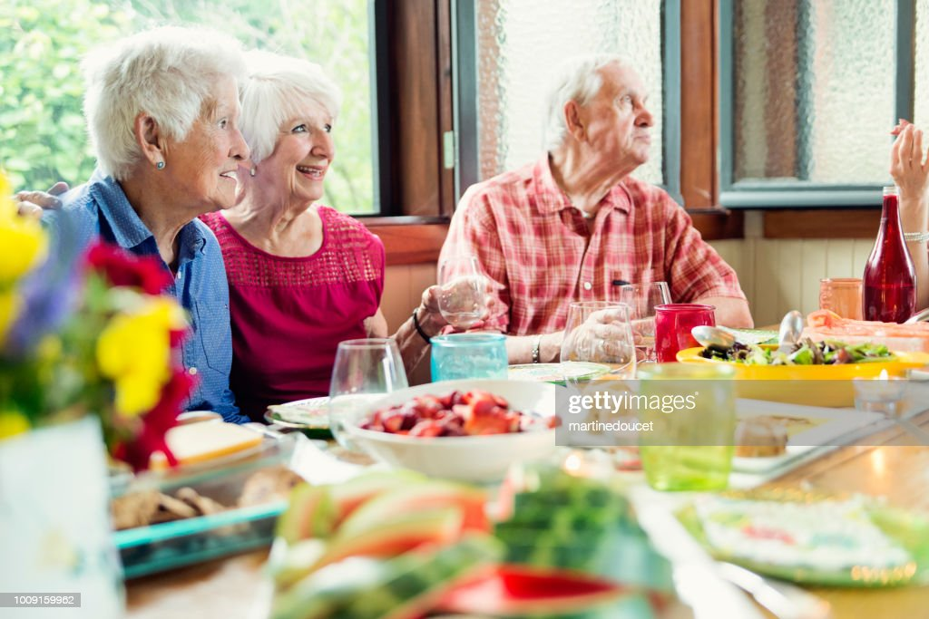 Group of seniors having dinner in summer house. : Stock Photo