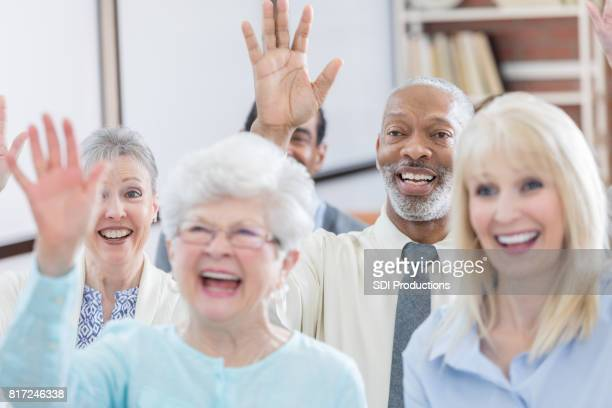 A group of seniors laugh and enjoy senior meeting entertainment together