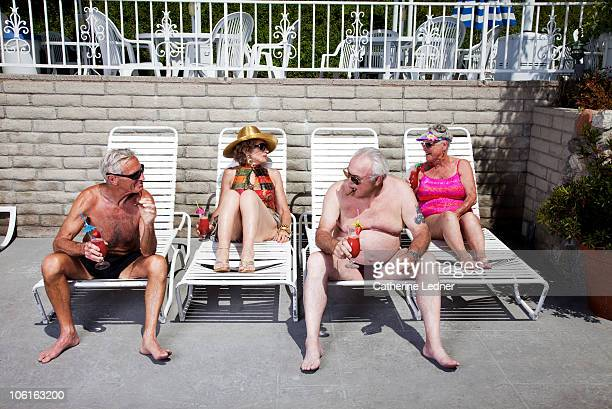 group of seniors laying out in bathing suits - man wearing speedo stock photos and pictures