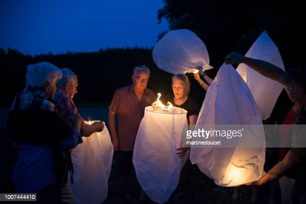Group of seniors lighting flying chinese lanterns at dusk.