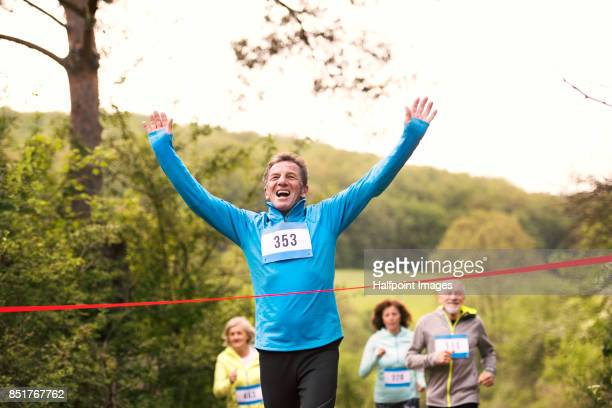 group of seniors running race in nature on dirt road. - finish line stock pictures, royalty-free photos & images