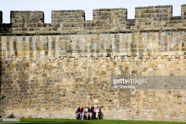 A group of seniors sat on a bench at Alnwick Castle
