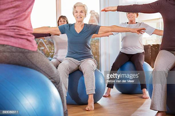 Group of seniors sitting on exercise balls.