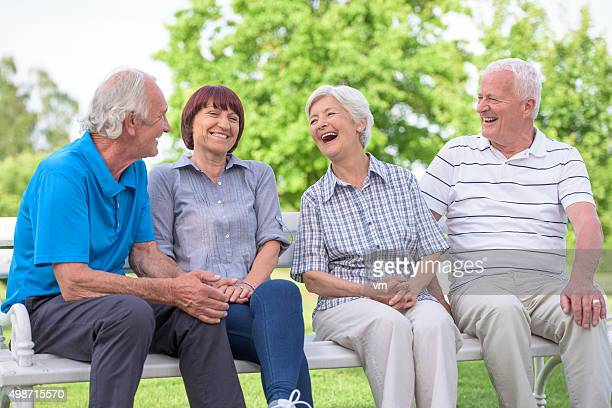 Group of seniors sitting on park bench laughing and smiling