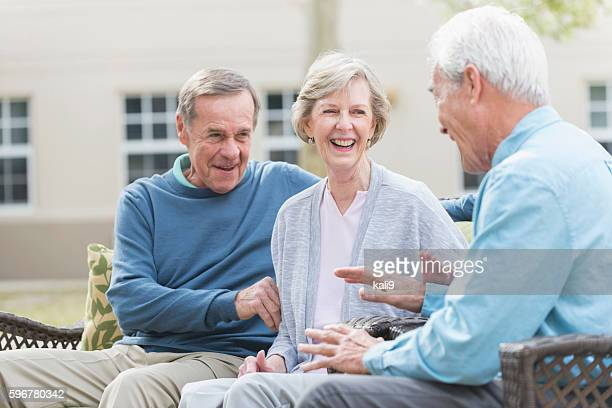 Group of seniors sitting outdoors, talking and laughing