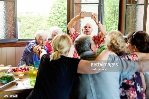 """group of seniors taking a selfie at dinner in summer house. - """"martine doucet"""" or martinedoucet stock pictures, royalty-free photos & images"""