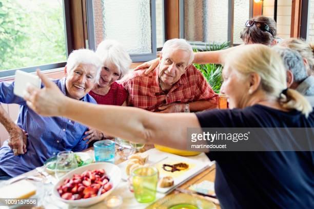 Group of seniors taking a selfie at dinner in summer house.