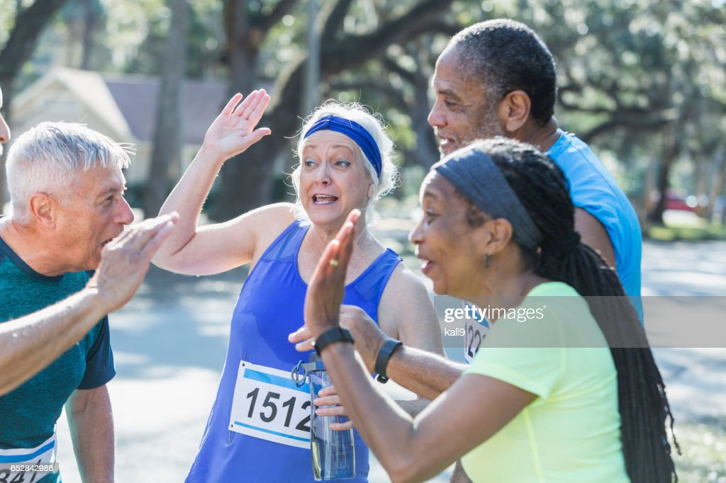 Group of seniors talking at end of race, high fives : Stock Photo