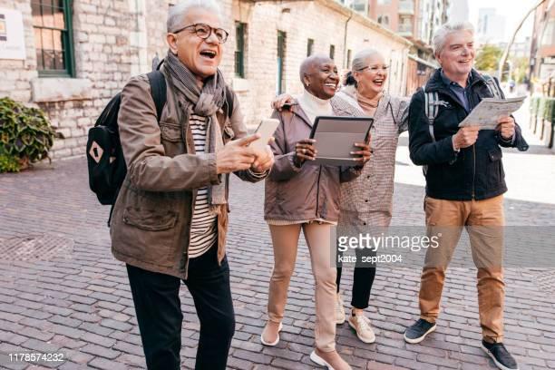 新しい都市を訪れる高齢者グループ - ツアーガイド ストックフォトと画像