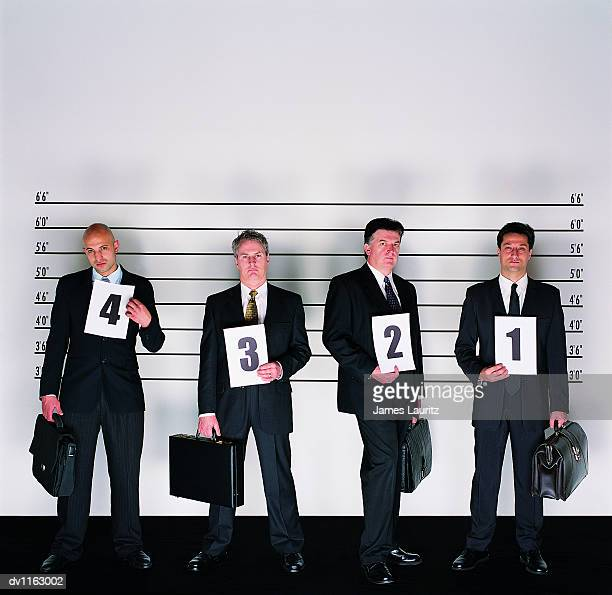 Group of Serious Businessmen Standing Holding Briefcases and Placards in a Police Line-up