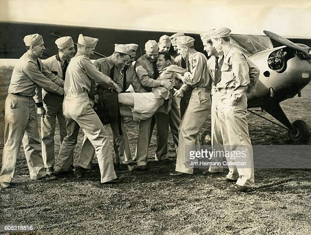 Group of servicemen holding a man and pulling off his pants They look like they are playing around They are standing next to a small plane