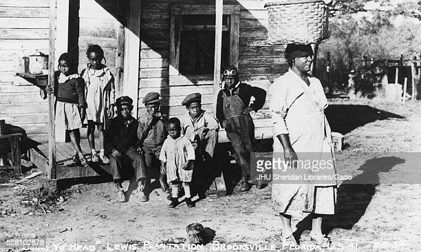 A group of seven young African American children with serious expressions are gathered on the porch of a shanty on the Lewis Plantation in...