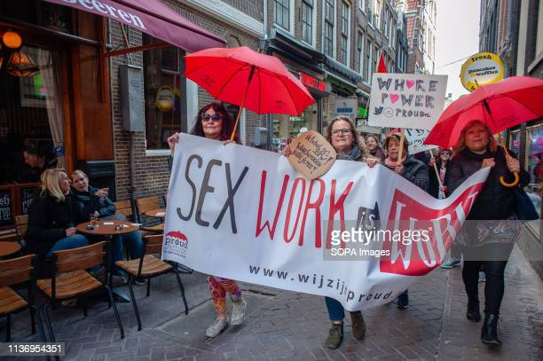 A group of sex workers and supporters are seen holding a banner red umbrellas and placards during the demonstration After a social media campaign...