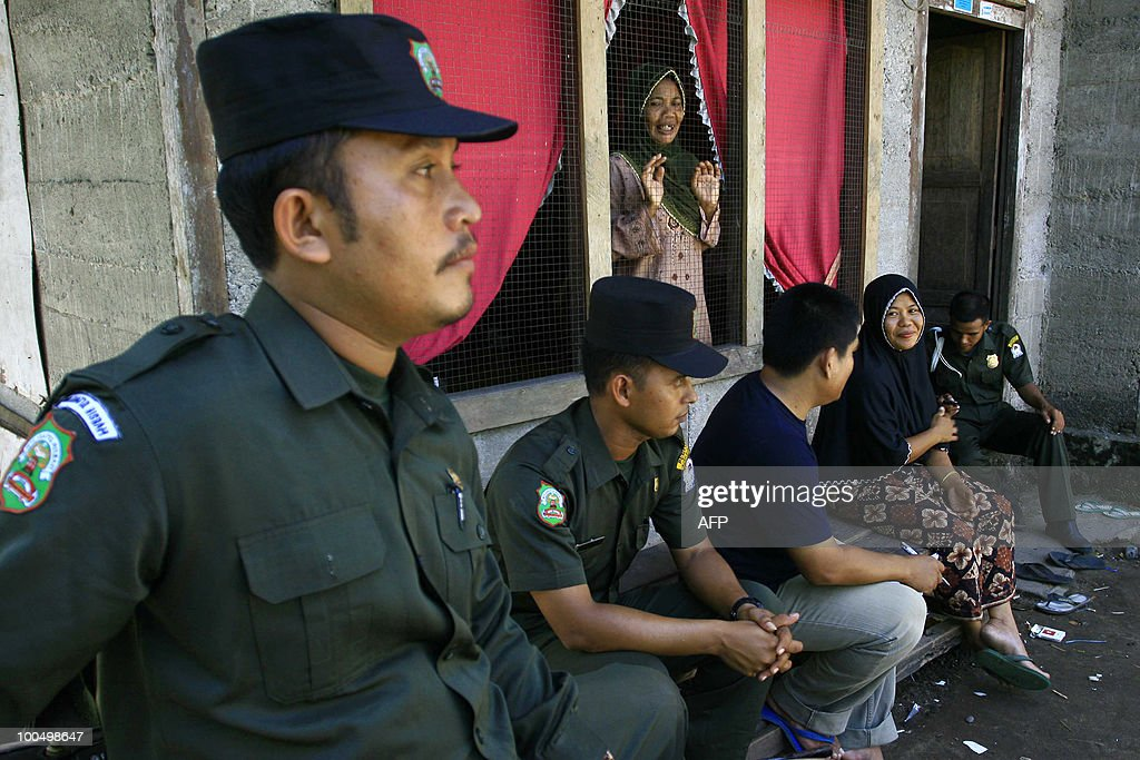 A group of Sharia policemen sit with a woman in Meulaboh village in West Aceh district of Aceh province during a campaign against women wearing tight pants and clothing in the district, on May 25, 2010. Local authorities are implementing Sharia (Islamic) law, which has been adopted by the provincial government and which stipulates that women can only show their face and their hands, according to sharia police officials. Aceh province runs under special autonomy and is one of the most conservative regions in the mainly Muslim archipelago having established a religious police force.