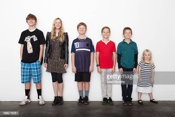 group of sibling in line against white wall - medium group of people stock pictures, royalty-free photos & images