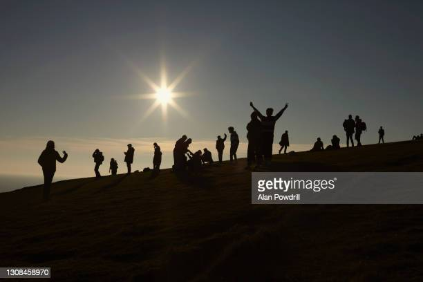 group of silhouetted people on hillside with sun behind - dawn stock pictures, royalty-free photos & images
