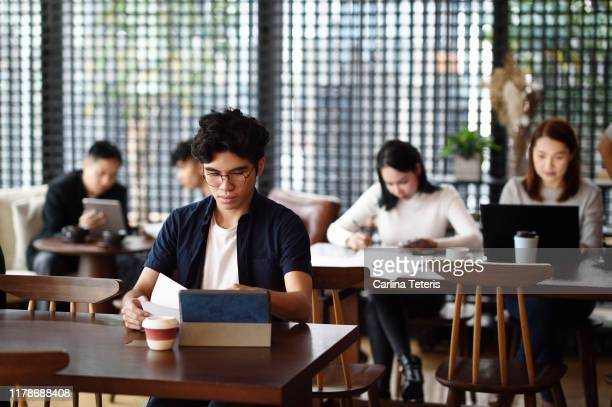 group of singaporeans working in a co-working office - thai ethnicity stock pictures, royalty-free photos & images