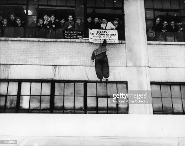 Group of sitdown strikers peer from the windows of the Chevrolet Plant in Flint, Michigan in December of 1936 after the start of a 43 day strike of...