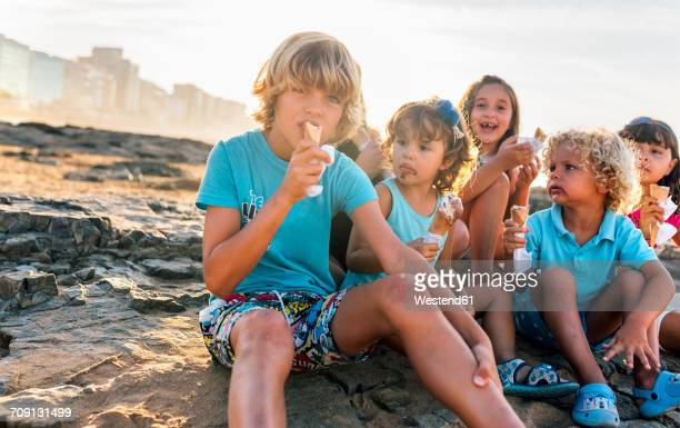 Group of six children eating icecream on the beach