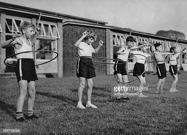 A group of six children play with hula hoop's outside on the grass circa 1960's
