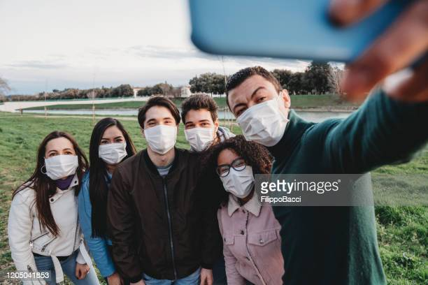 group of six friends taking a selfie together while they are wearing protecting masks - coronavirus italia foto e immagini stock