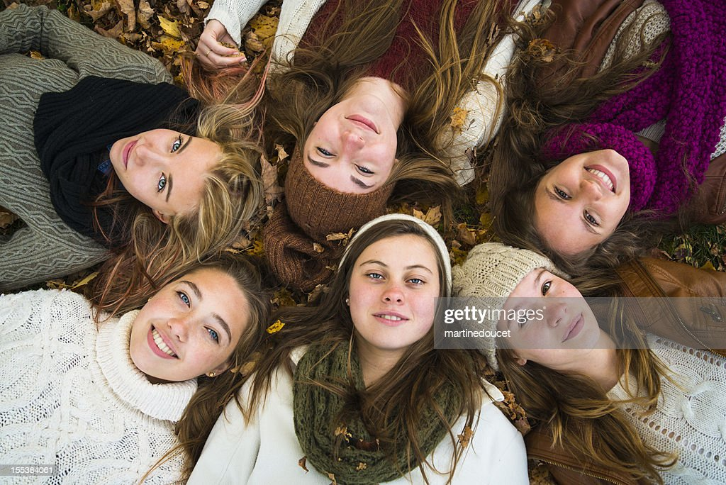 Group of six girls lying down in fallen leaves : Stock Photo