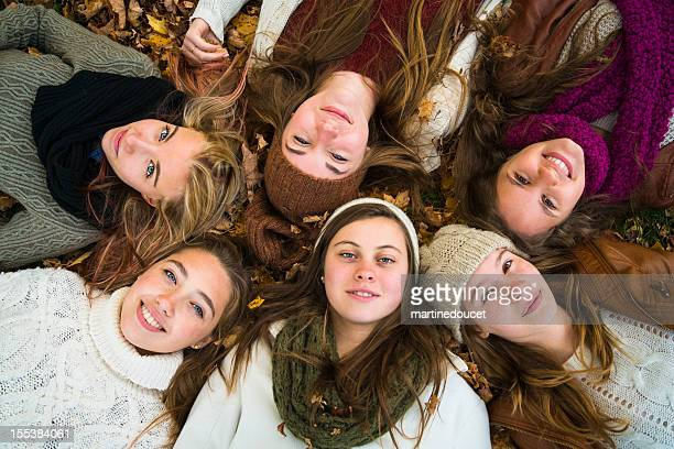Group of six girls lying down in fallen leaves