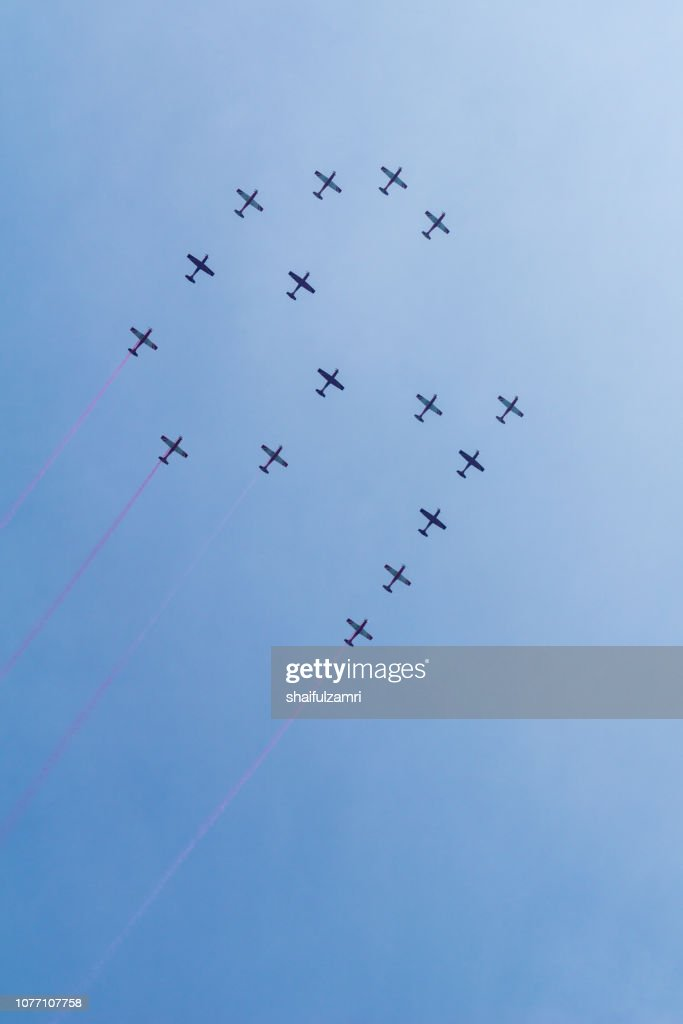 Group of sixteen Malaysian military fighter jet planes flying in a 61 formation high in blue sky during 61st of National Day parade air show. : Stock Photo