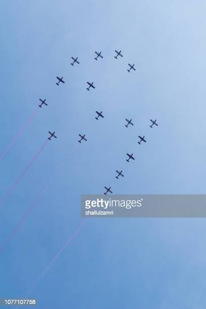 Group of sixteen Malaysian military fighter jet planes flying in a 61 formation high in blue sky during 61st of National Day parade air show.