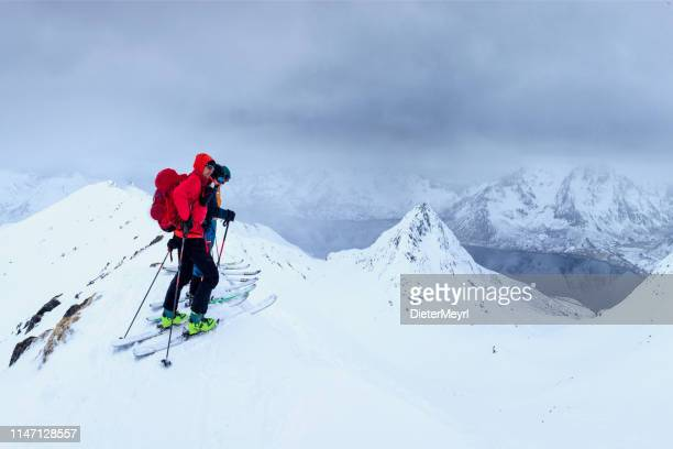 group of ski tourers in bad weather on the summit,  lofoten - norway - nordic skiing event stock pictures, royalty-free photos & images