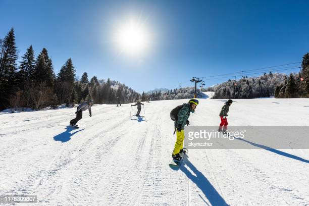 group of skiers and snowboarders on a ski slope. - snowboarding stock pictures, royalty-free photos & images